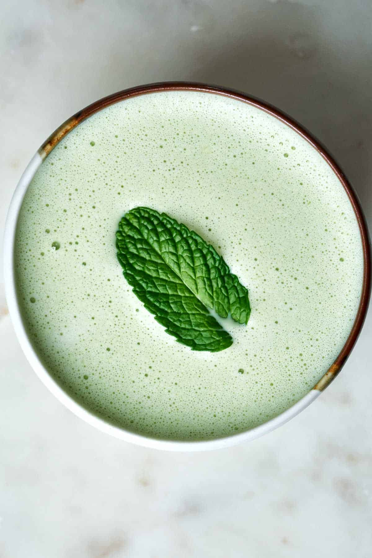 Green latte with a mint leaf on top.