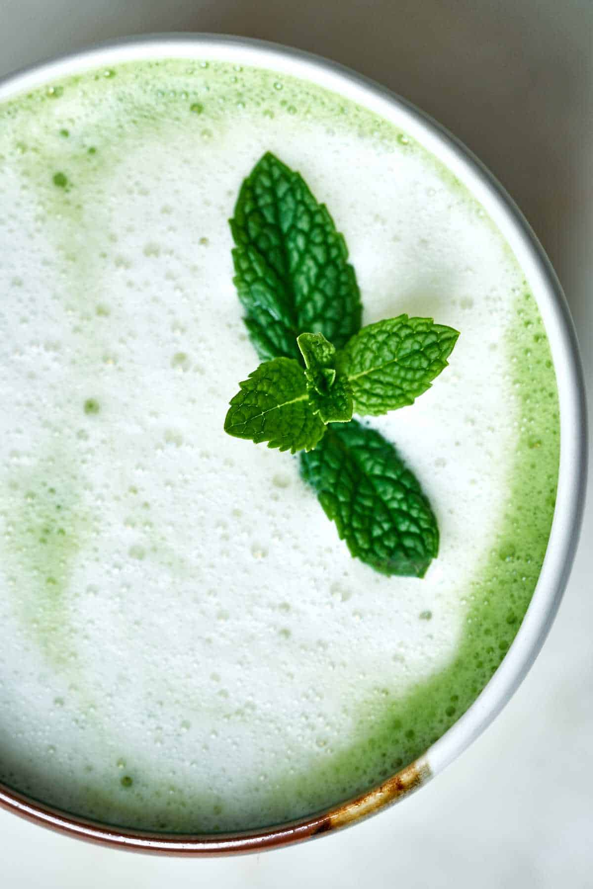 Close up of mint on a green tea latte.