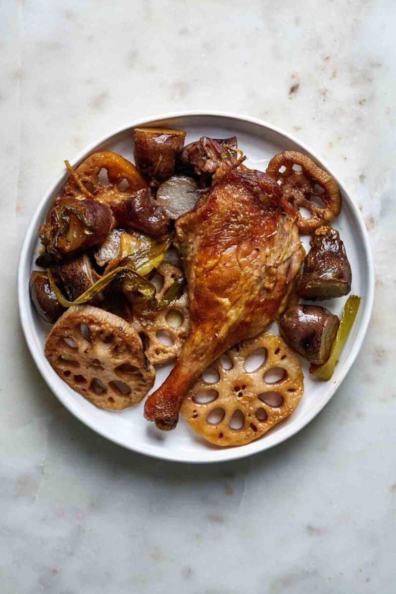 Duck leg dinner on a plate.