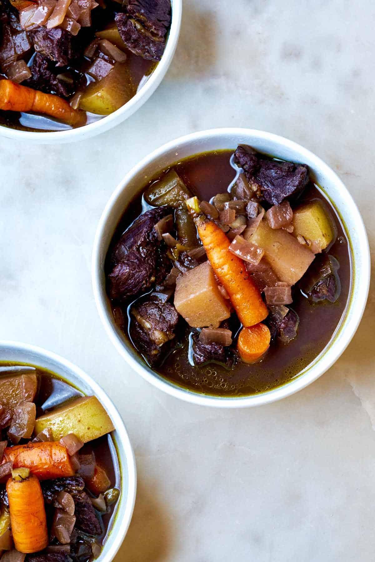 Three bowls of beef stew.