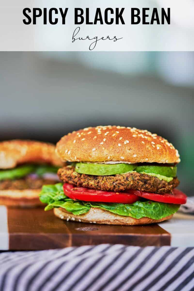 Two burgers on a cutting board.