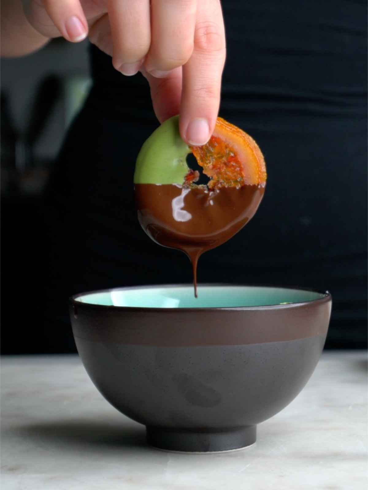 Dipping a candied orange in chocolate.