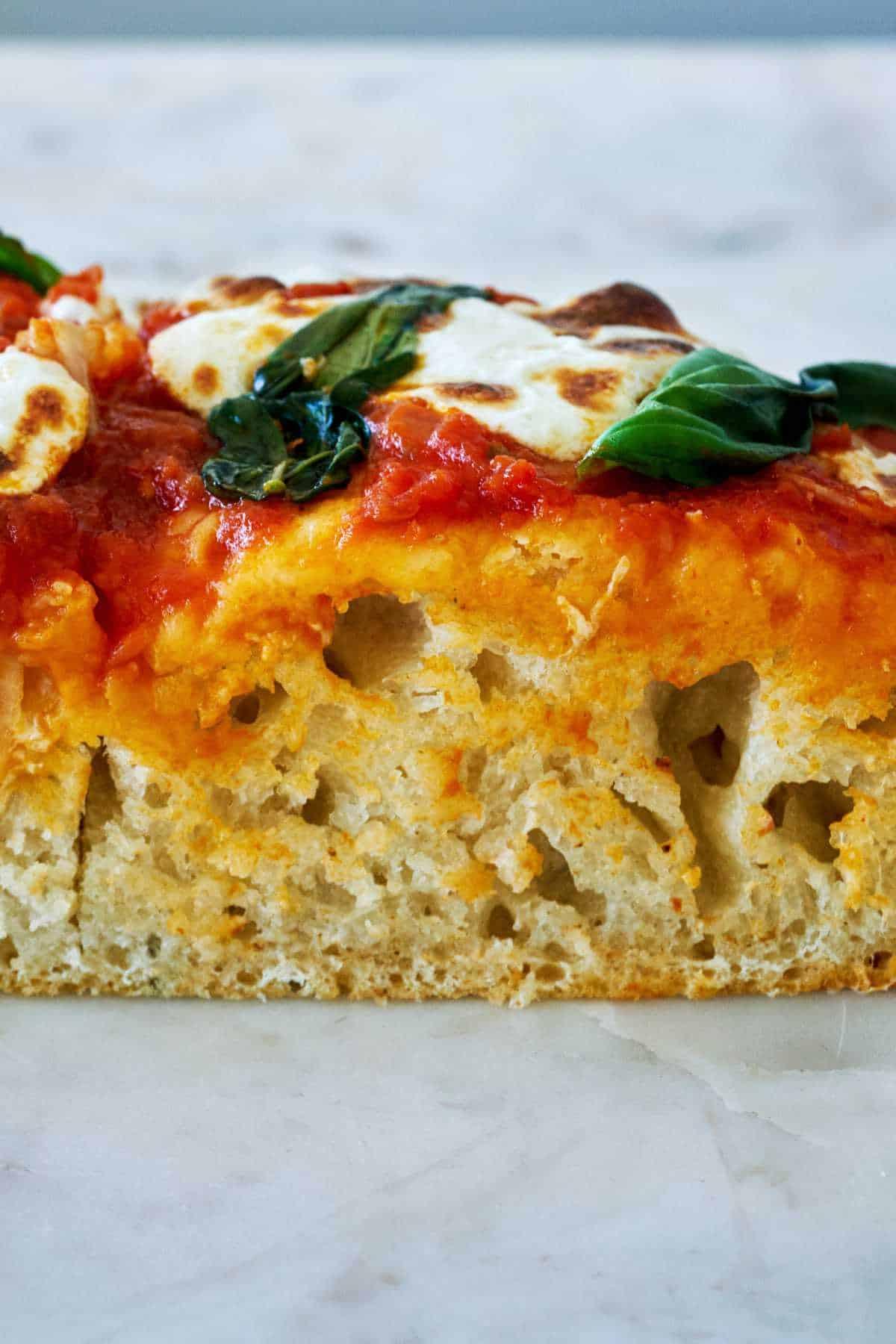 Slice of thick focaccia pizza.