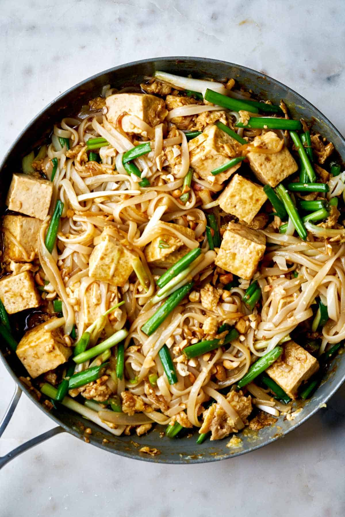 Noodles and tofu in a fry pan.