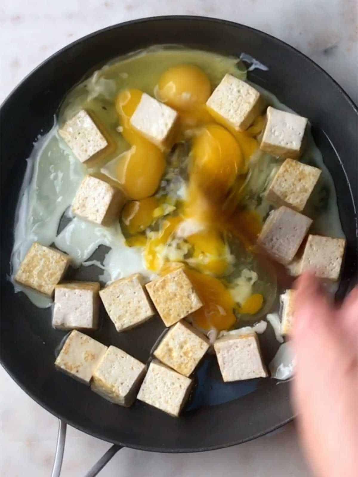 Scrambling eggs and tofu in a pan.