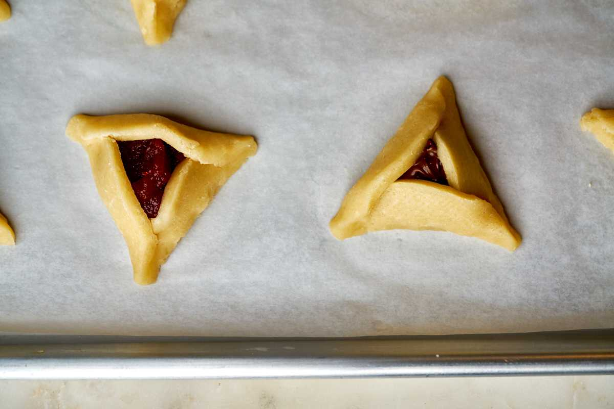 Triangle cookies on a baking sheet.