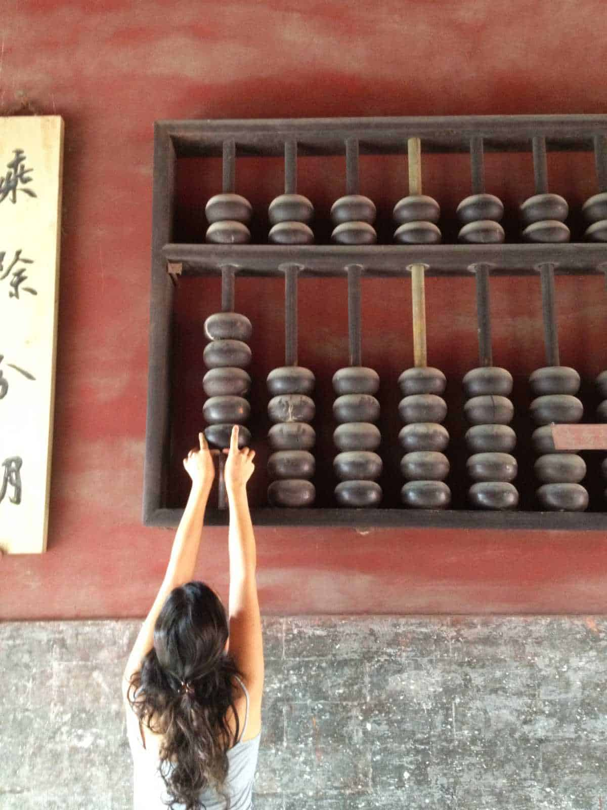 Woman moving a giant abacus.