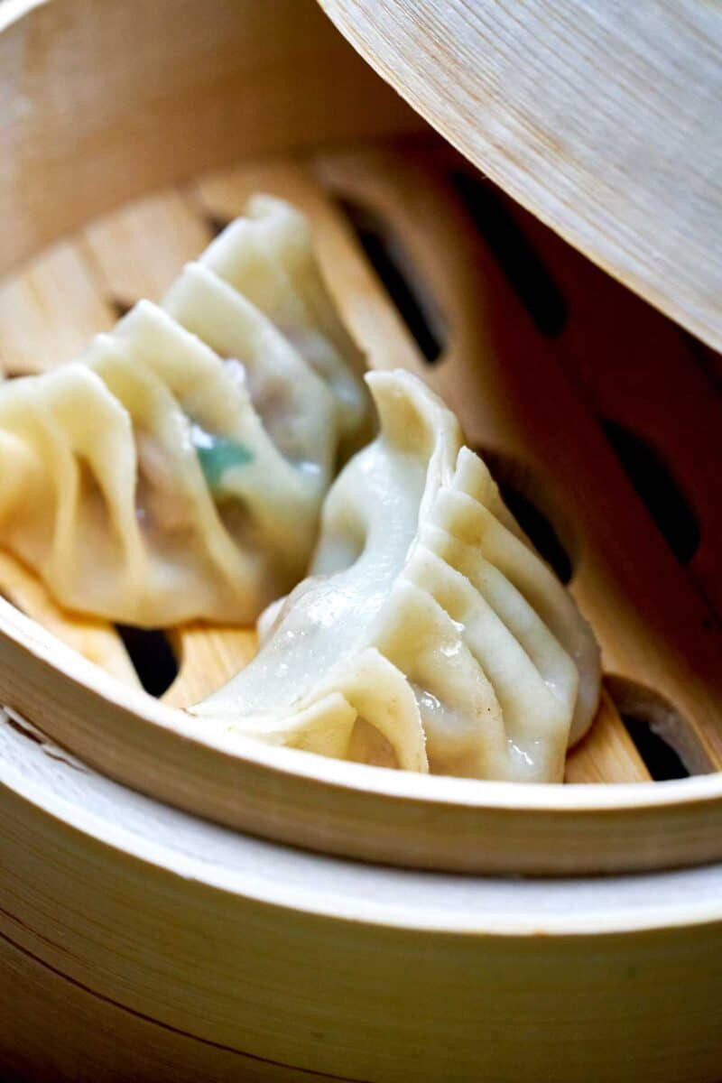 Two dumplings in a small steamer.