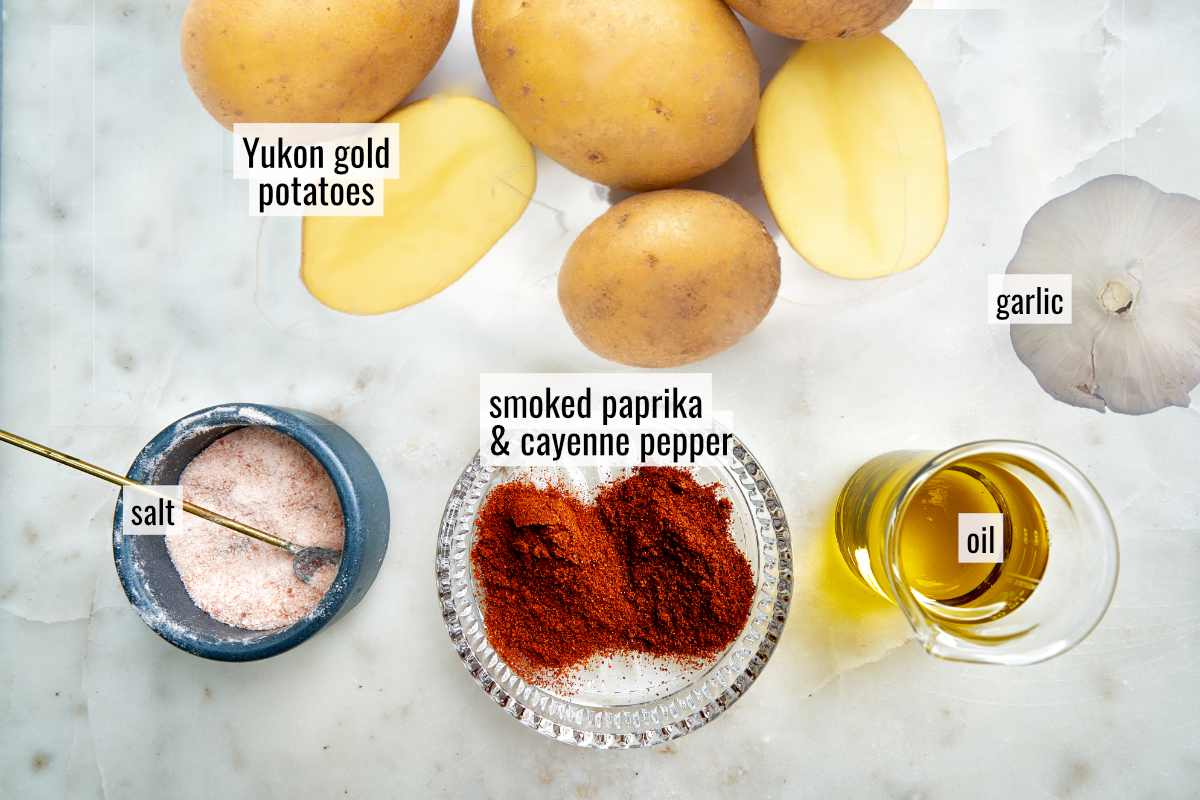 Potatoes and spices on a white countertop.