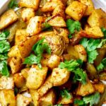 A plate of potatoes with cilantro and salsa.