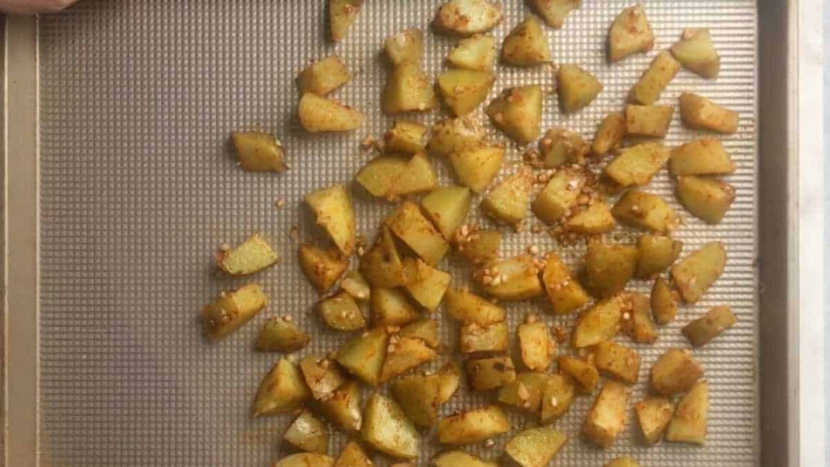 Baking sheet with diced potatoes.