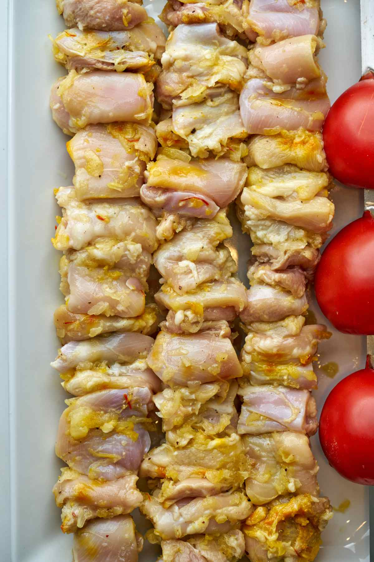 Raw chicken kabobs next to tomatoes.