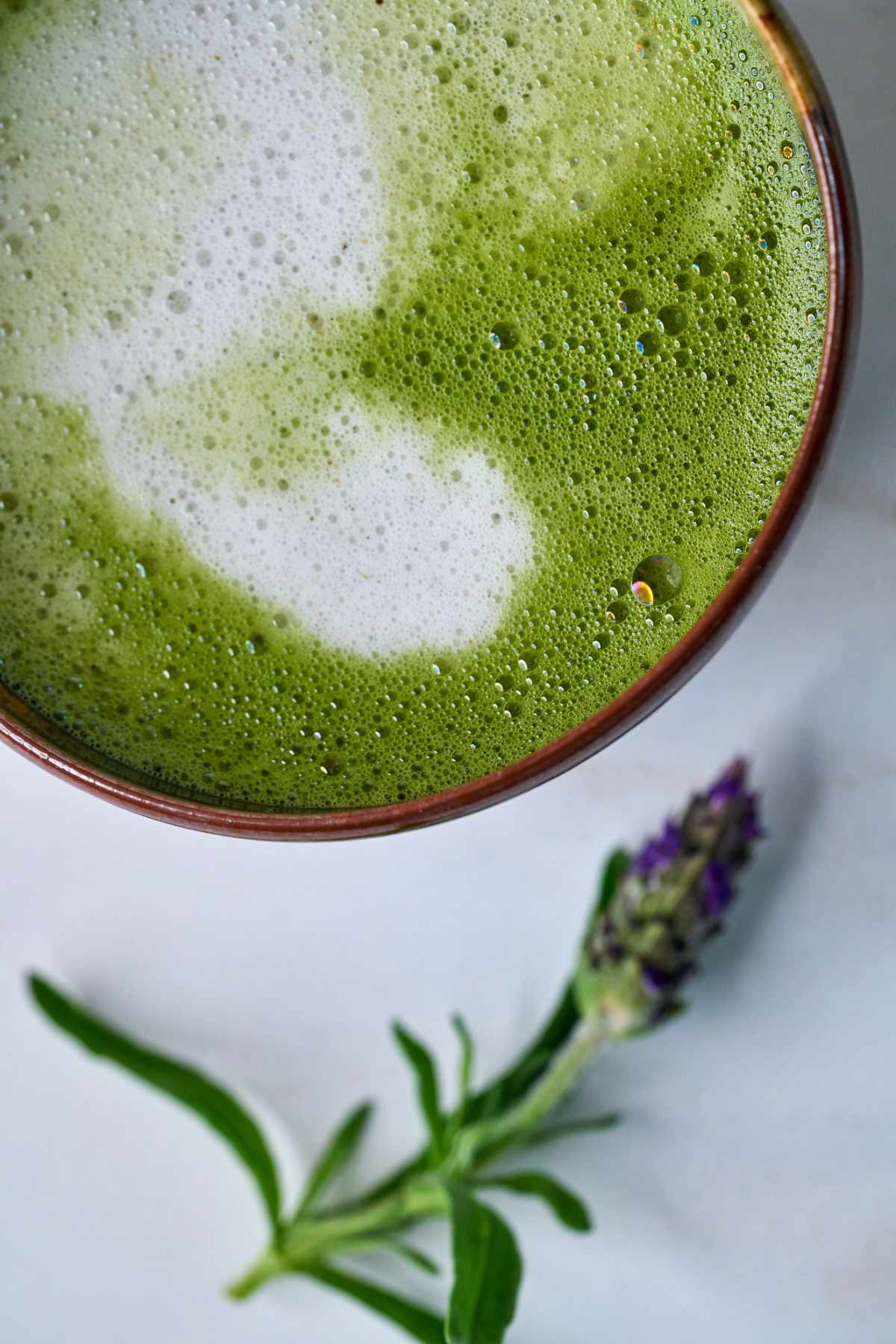 Green latte next to a sprig of lavender.
