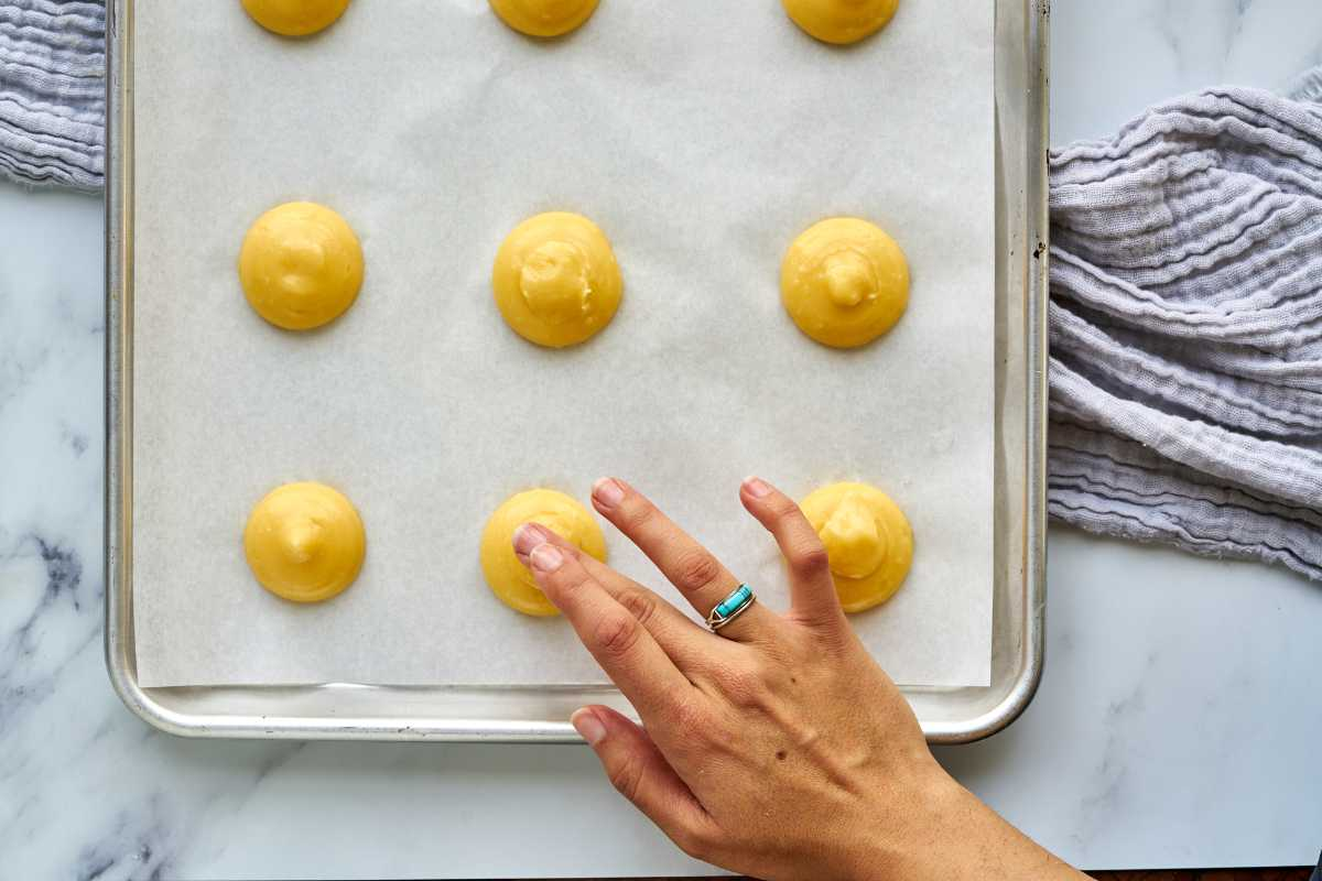 Smoothing the tops of raw choux dough with a finger.