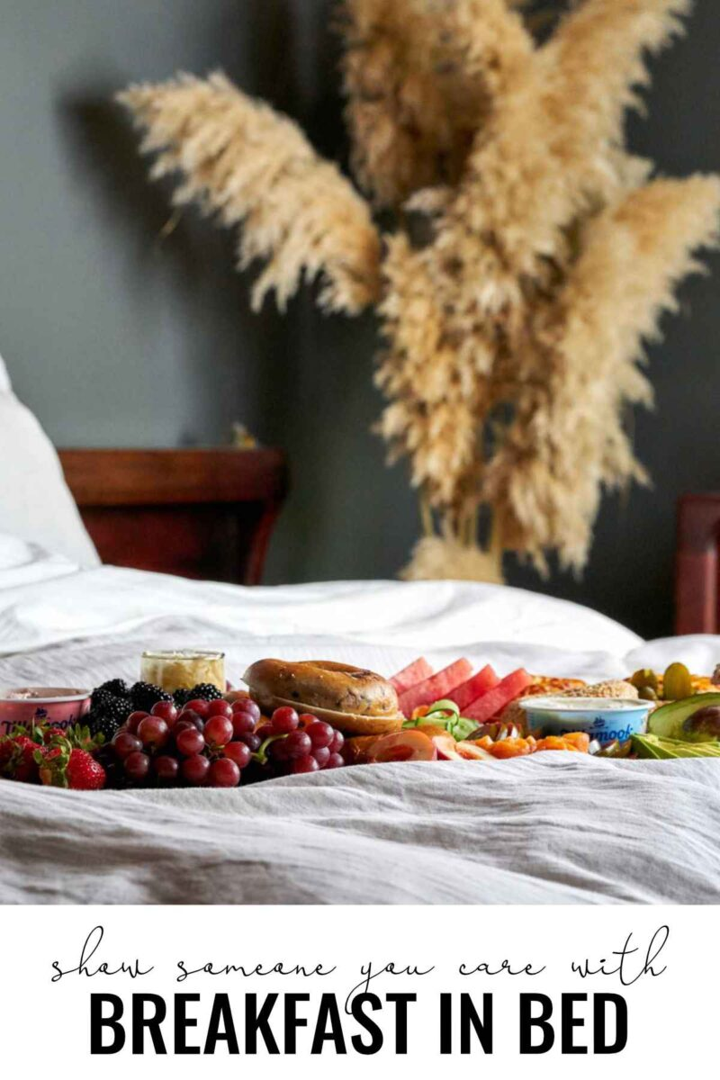 Breakfast board in a bed with pampas grass.