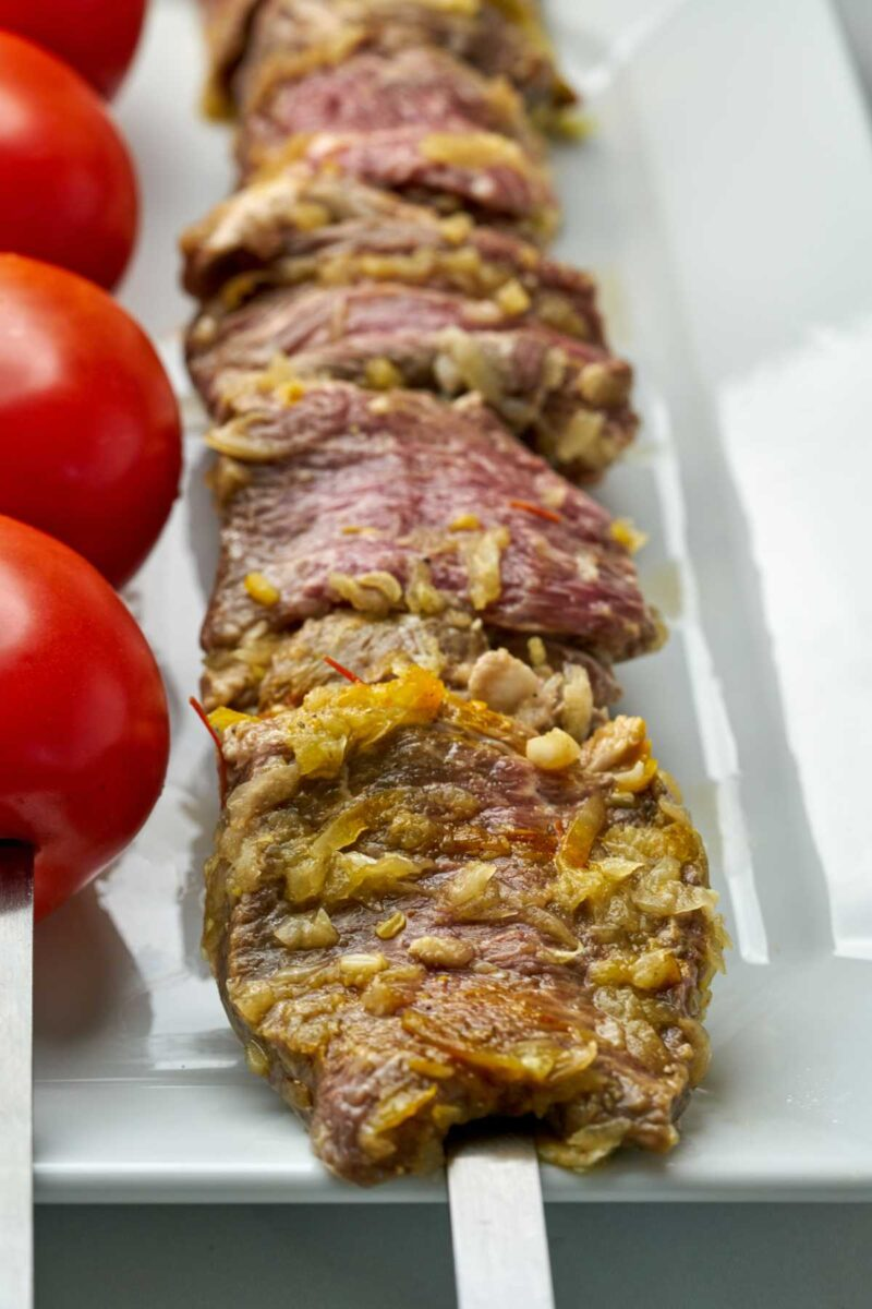Raw kabob and tomatoes on a plate.