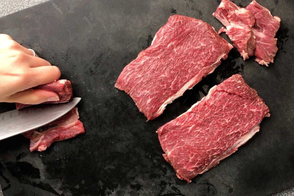 Raw meat on a cutting board.