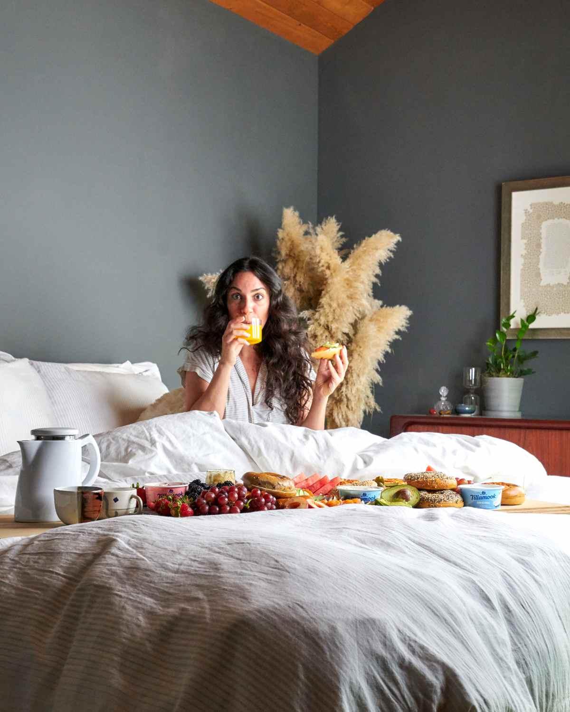 Woman in bed eating breakfast.